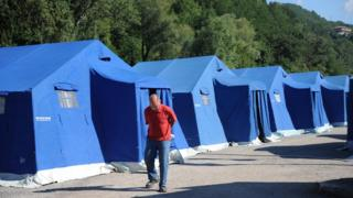 A man walks down a row of tents.