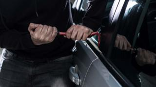 File image of a man breaking into a car