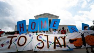 Activists hold up a sign reading Home outside the US Supreme Court