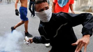A protester throws back a tear gas canister during clashes with security forces in Caracas on 23 January