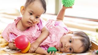 Bhutanese twins Nima and Dawa Pelden play with toys