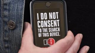 Protester holds phone with banner, rejecting consent to search the device