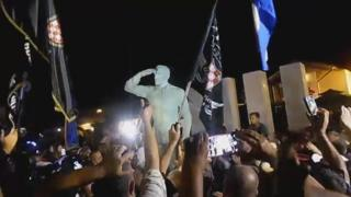 A grab from a video of the unveiling ceremony, showing crowds around the statue
