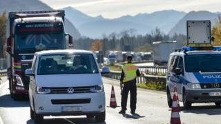 A police officer surveys cars and trucks queuing to cross the Austria-Germany border at the southern German city of Kiefersfelden, 3 Nov 2015
