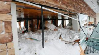 Snow is seen covering the inside room of a hotel, piled high enough to touch the ceiling lampshades, while the windows are shattered and broken