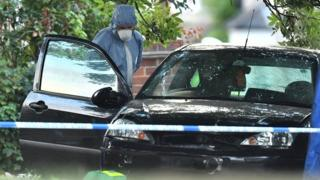 Forensic police officer examining car in Lennard Road