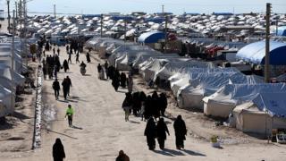 Mulheres caminham em campo na Síria, em abril de 2019