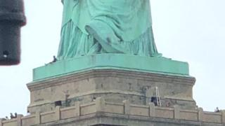 A person is spotted sitting at the base of the Statue of Liberty in New York, 4 July 2018