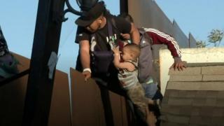 رجل وطفله يستلقان سياجا حدوديا يفصل بين المكسيك والولايات المتحدة، طلبا للجوء، ولكن دورية لحرس الحدود الأمريكي اعتقلته في الحال.