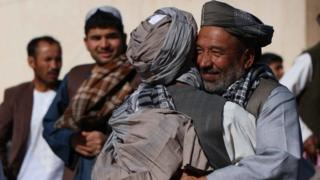 Afghans greet each other after offering special prayers on on Eid al-Fitr in Herat, Afghanistan, 15 June 2018.
