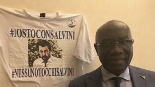 Tony Iwobi debout à côté d'un t-shirt Salvini
