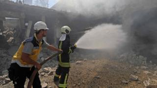 Syrian firefighters try put out a fire in a building that was hit by reported Russian air strikes in the rebel-hold town of Jadraya, about 35km south-west of the city of Idlib, on September 4, 2018