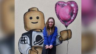 Hollie Evans in front of Lego man artwork