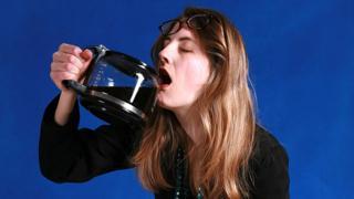 Mujer exhausta tomando café directo de la cafetera