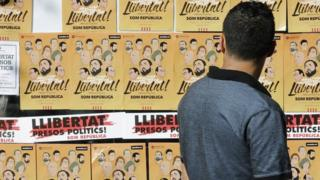 A man looks at posters during a demonstration to protest against the imprisonment of eight former members of Catalan government