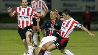 A Derry City player tackles a PSG player during a game in 2006