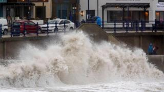 in_pictures Pedestrians walk along the promenade as huge waves crash against the sea wall at Porthcawl, south Wales