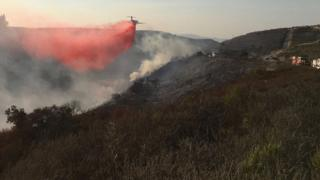 Undated photo obtained from the Santa Barbara County Fire shows firefighting tanker airplanes dropping retardant on the Thomas Fire