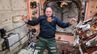 Astronauta tentando comer cenouras enquanto flutuam no espaço