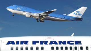 The top of a plane, sporting the AIR FRANCE logo, occupies the bottom third of this photo, while a blue KLM plane hovers over it.