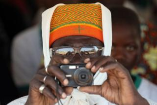 A man takes a picture during the inauguration ceremony of the solar energy power plant in Zaktubi, near Ouagadougou, on november 29, 2017, on the second day of France's President Emmanuel Macron first African tour since taking office.