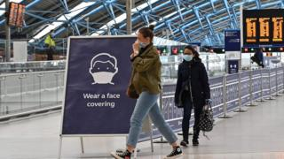 "A sign tells passengers to ""wear a face covering"" at Waterloo train station in central London"
