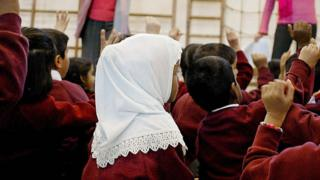A young girl wearing a Muslim headscarf listens as two teachers instruct a class.