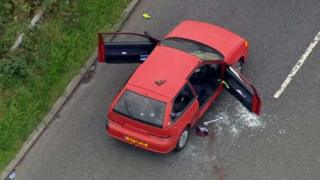 Aerial shot of red car showing bullet holes