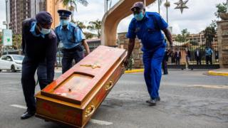 Kenyan police officers remove an empty coffin left after the protest against police brutality in Nairobi on June 9, 2020.