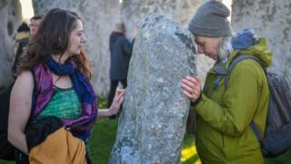Люди обіймають камені