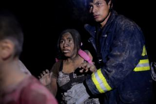 A rescue worker and a woman covered with ash
