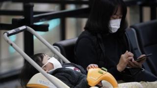 Mulher e criança com máscaras no aeroporto internacional de Tóquio