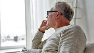 Man sitting and staring out of window