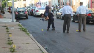 Baltimore police detectives on the scene of a homicide in the Pigtown neighbourhood