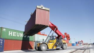 A shipping container is lifted at a rail port on August 18, 2018 in Erenhot, Inner Mongolia Autonomous Region of China.