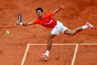 Tennis player Novak Djokovic leaps to bat the ball back