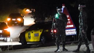 Military police secure the road as large convoy of official vehicles enter the Tham Luang cave area
