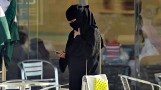 Woman looks at phone in Saudi Arabia