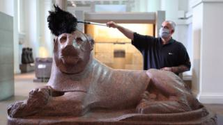 Man in a mask dusting a lion sculpture in the British Museum ahead of reopening on 27 Aug