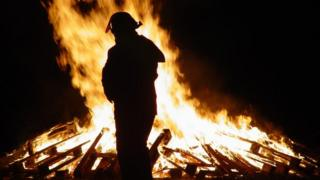 Silhouette of firefighter and bonfire