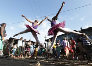 Young ballerinas from different schools perform a dance during a ballet street performance to showcase their skills in Kibera slum, Nairobi, Kenya - Friday 30 November 2018