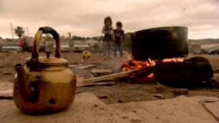 Kettle and camp fire, children in the background playing with a ball