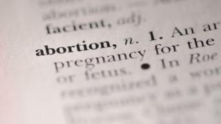 The word 'abortion' highlighted in a dictionary