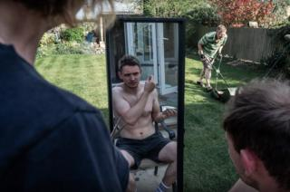 Man cuts his own hair in mirror as garden as other man mows the lawn