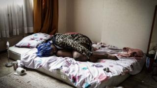 A woman lying on a bed - photo from NCA's 'Invisible People' exhibition
