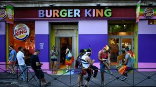 People loiter outside a Burger King during a Pride event