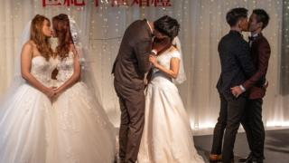 Three couples kiss during wedding ceremony