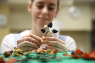 Baker Sophie Cabot puts the finishing touches to cake decorations for the red velvet and chocolate wedding cake for Princess Eugenie of York and Mr Brooksbank in the kitchens at Buckingham Palace on October 10, 2018 in London, England