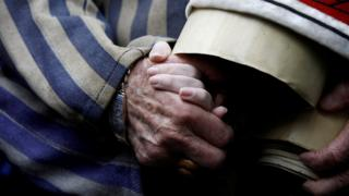 Holocaust survivor Edward Mosberg holds the hand of his granddaughter Jordana Karger