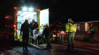 Patient being wheeled into an ambulance at night